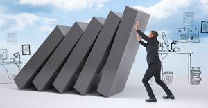 Businessman with his hands up against falling blocks
